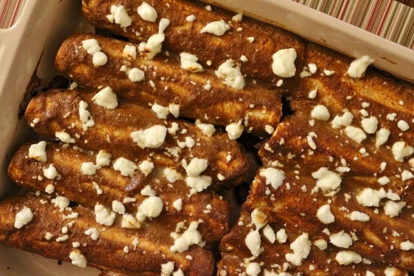 overhead view of a baking dish of enmoladas (enchiladas with mole sauce)