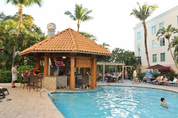 A swimming pool with a small pool bar shaped like a hut next to it