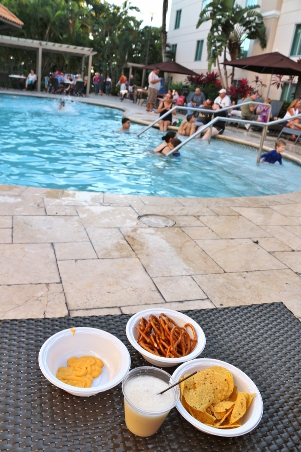 plates of snacks and a drink on a table next to a hotel pool