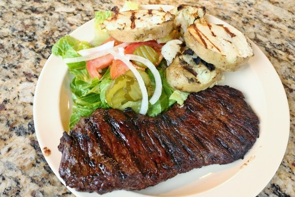 steak served with grilled potatoes and salad on a plate