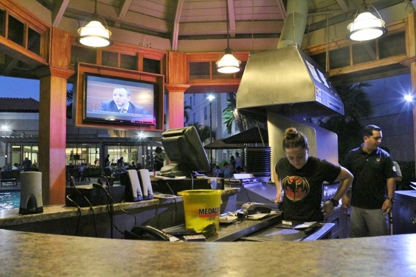 a woman in the kitchen area of an outdoor bar and grill
