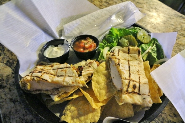 a grilled chicken quesadilla served with tortilla chips and salad