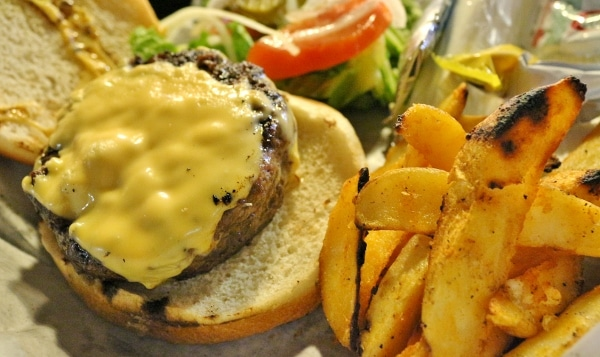 overhead view of a cheeseburger without the top bun, served with potato wedges