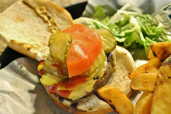 sliced pickles and tomato on a cheeseburger