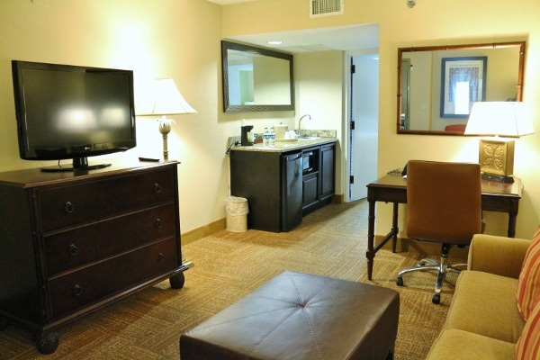A living room area in a hotel room with a television and a desk