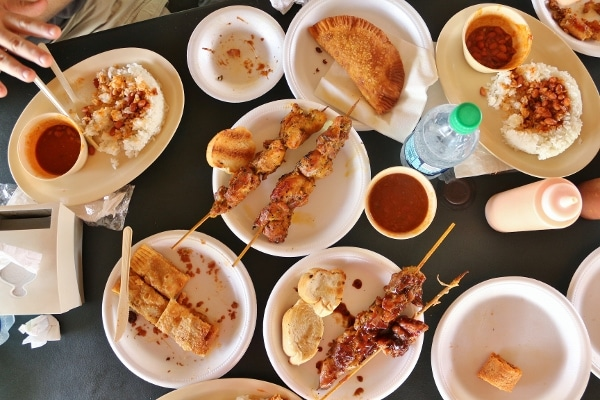 overhead view of skewered meats and fried empanadas on a table
