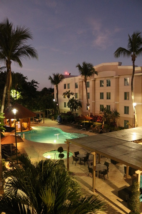 an outdoor pool surrounded by palm trees in the early morning hours before dawn