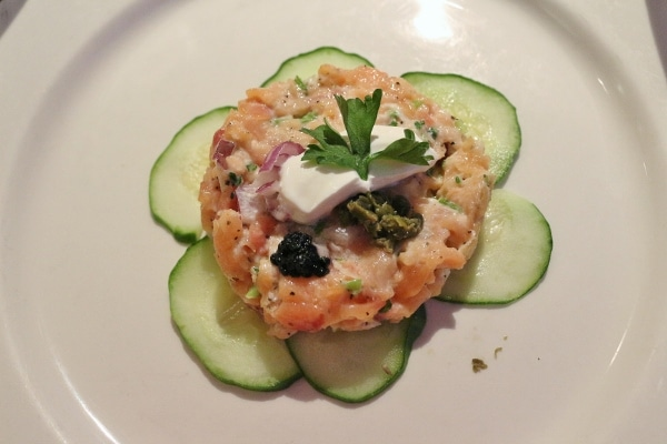 A plate of salmon tartare served over cucumber slices