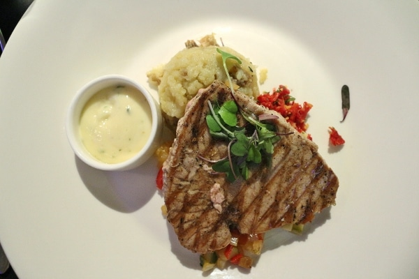 a grilled tuna steak with mashed potatoes and sauce on the side