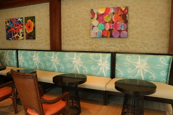 a booth sitting area with brightly colored cushions and wall paintings