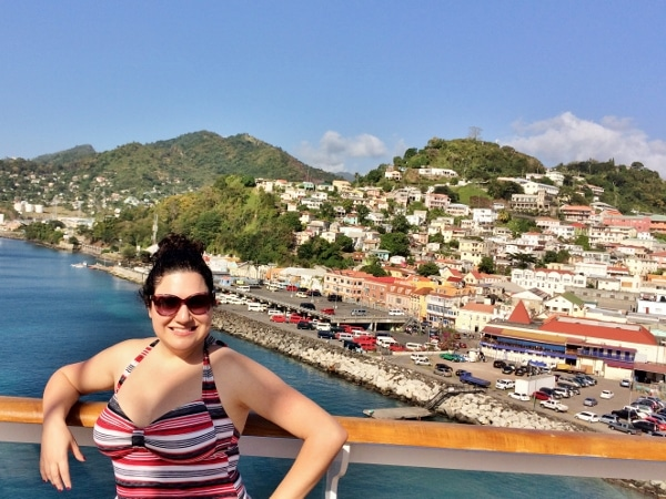 A woman posing on a cruise ship with Grenada in the background