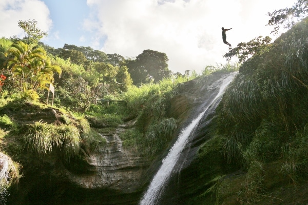 a man jumping from the top of a waterfall