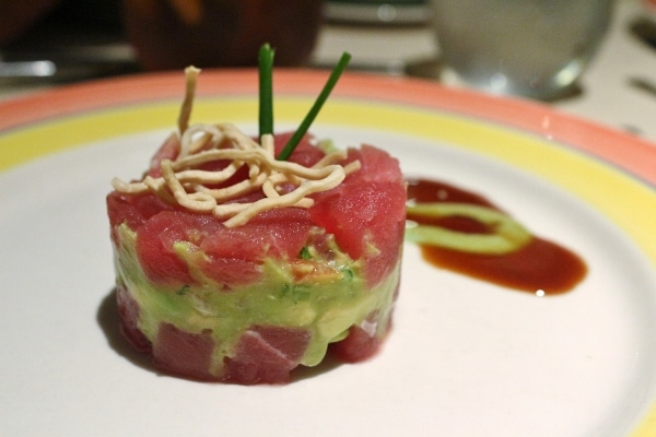 a raw tuna and avocado tower on a plate with sauce on the side