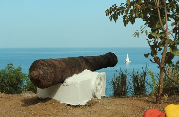 an old metal cannon pointing toward the sea in the direction of a sailboat