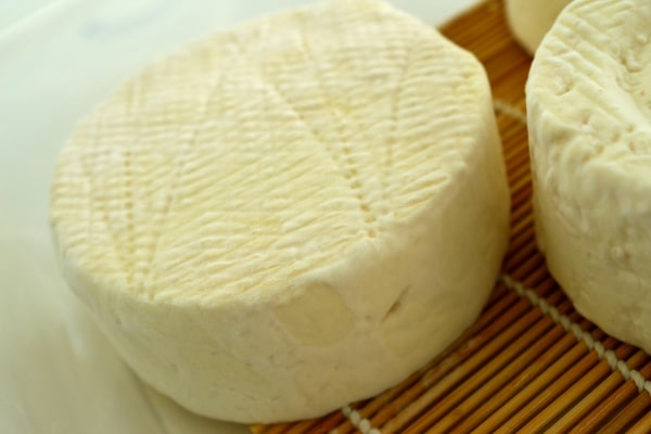 A close up of a wheel of partially aged Camembert with minimal mold growth