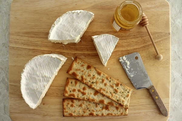 overhead view of a cheese board with Camembert cheese, crackers and honey