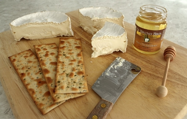 a wooden board topped with Camembert cheese, crackers, and white truffle honey