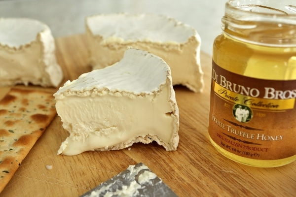 a closeup of Camembert cheese and white truffle honey on a wooden board