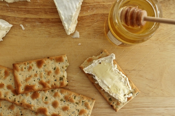 a slice of Camembert cheese on a cracker with honey over the top