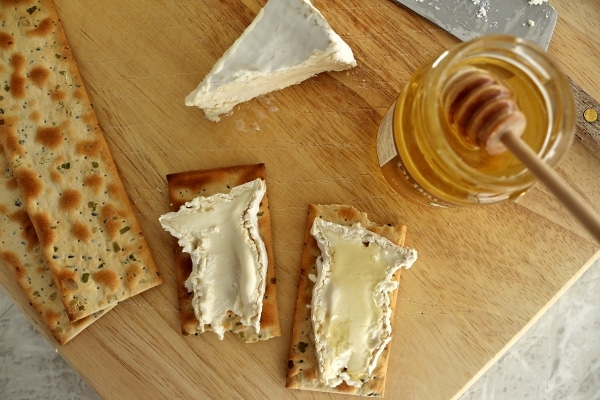overhead view of two slices of Camembert cheese on crackers with honey