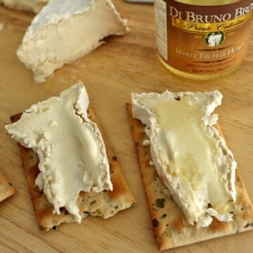 a closeup of two slices of Camembert cheese on crackers with white truffle honey