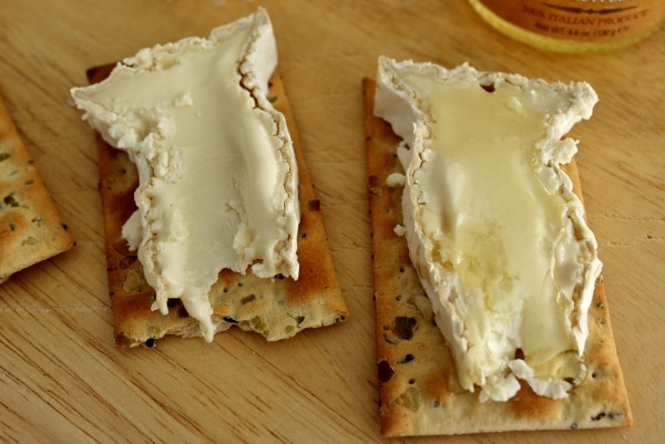 a closeup of two slices of Camembert cheese on crackers