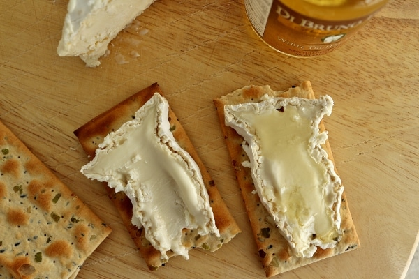 overhead view of two slices of ripe Camembert cheese on crackers