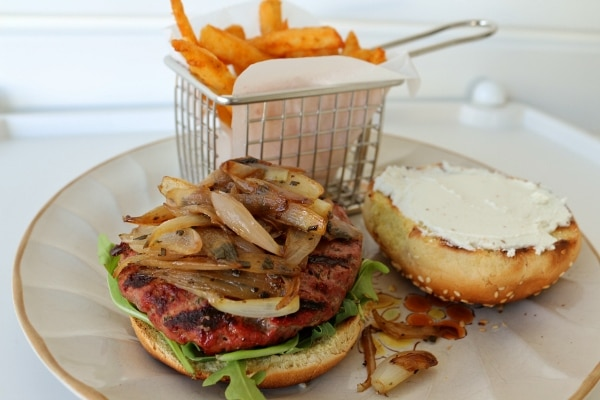 a burger with shallots and goat cheese, and fries on a plate