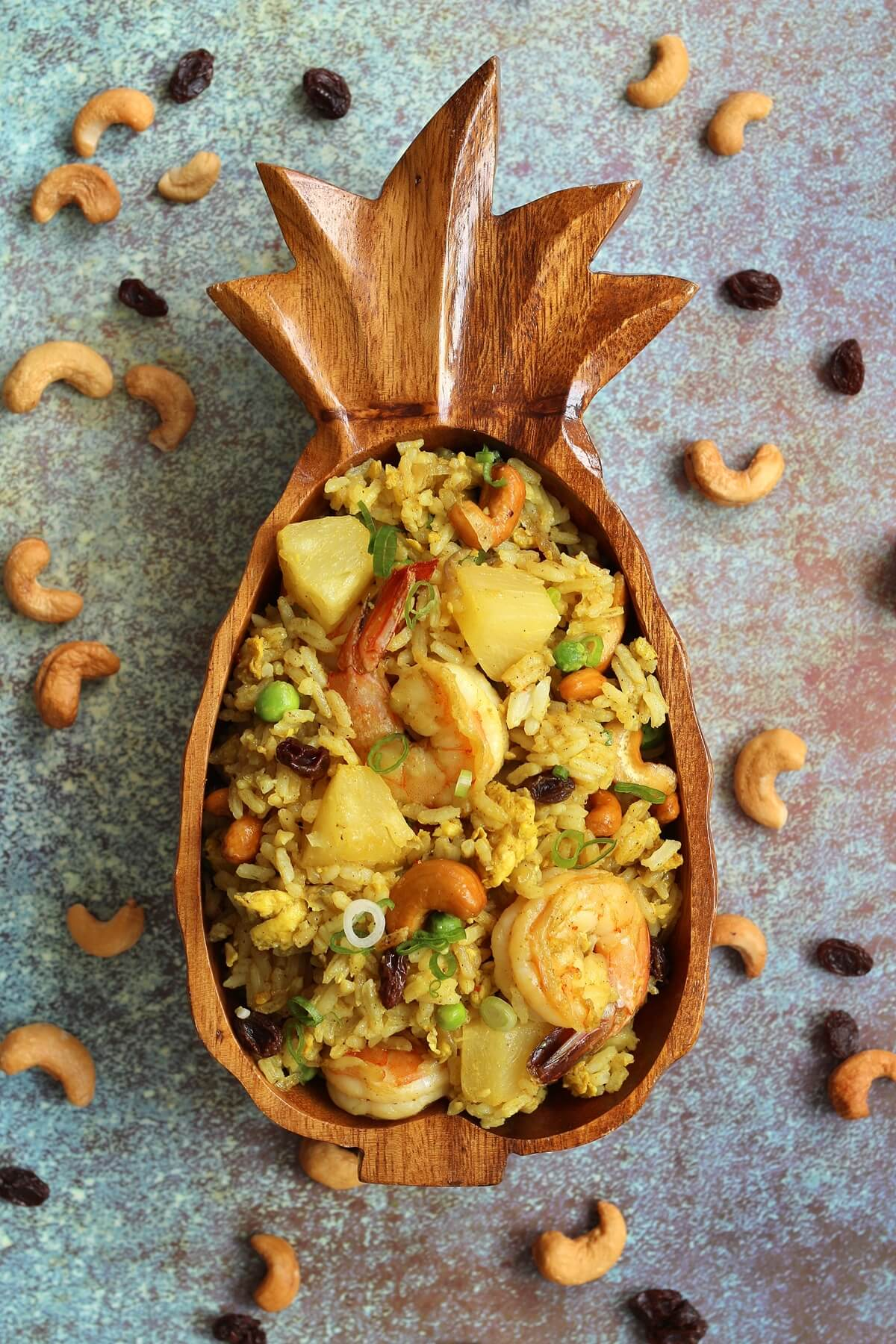 overhead view of fried rice in a pineapple bowl with cashews and raisins scattered around it
