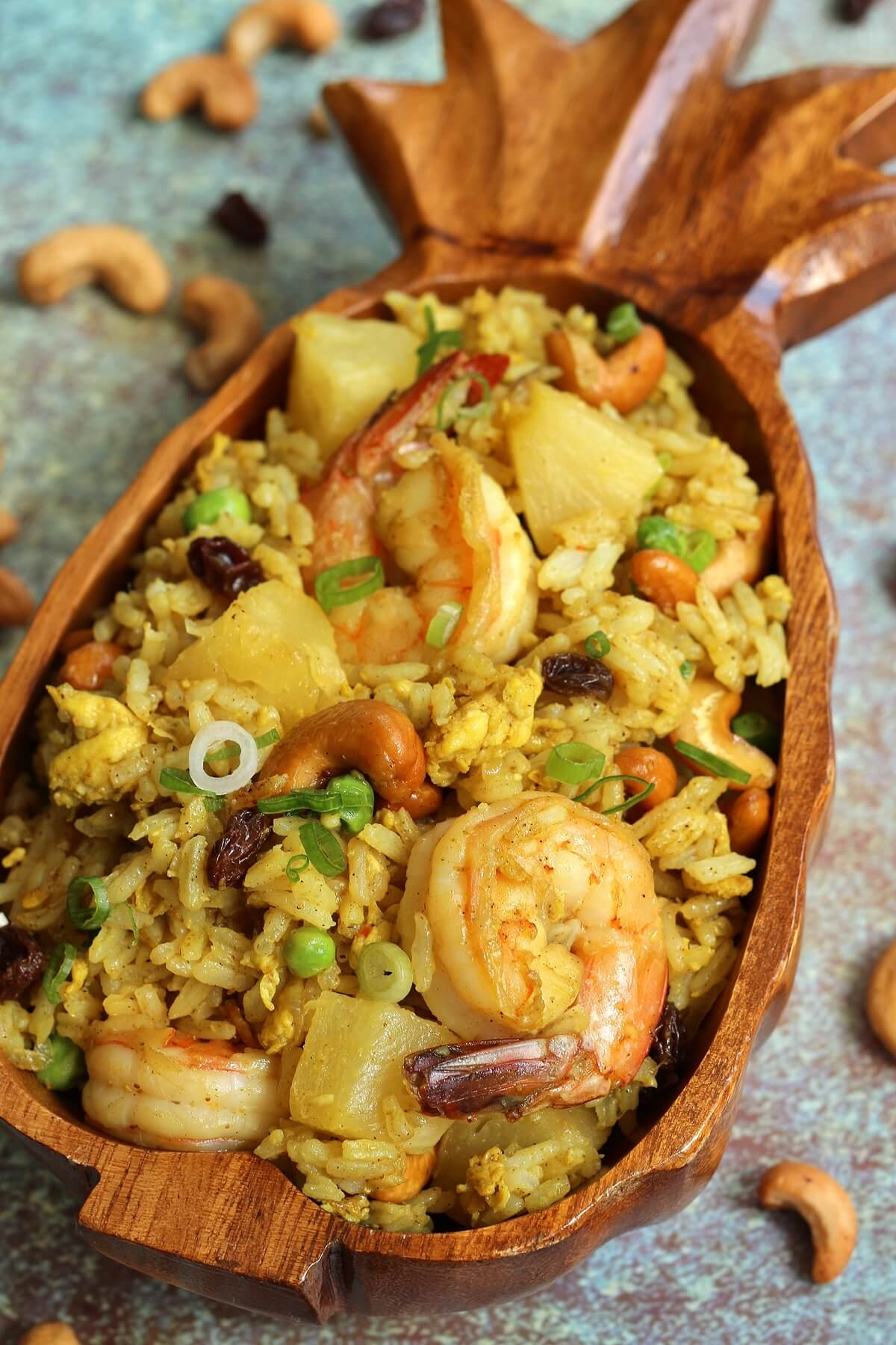 a wooden pineapple shaped bowl filled with Thai pineapple fried rice with shrimp