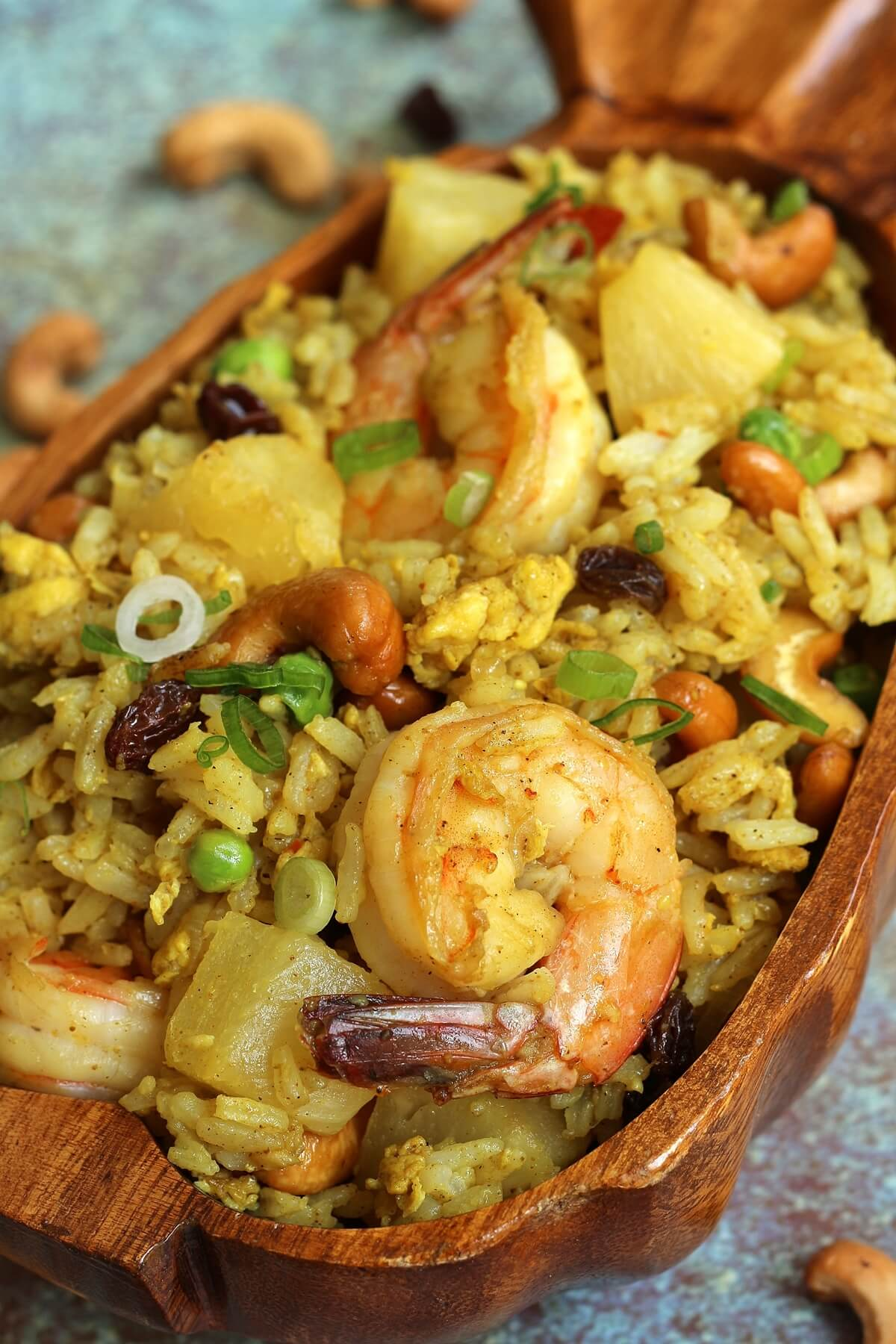 closeup of Thai pineapple fried rice with shrimp in a wooden pineapple bowl
