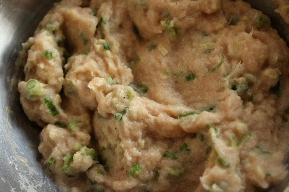 Pureed white fish filling with scallions in a small metal bowl.