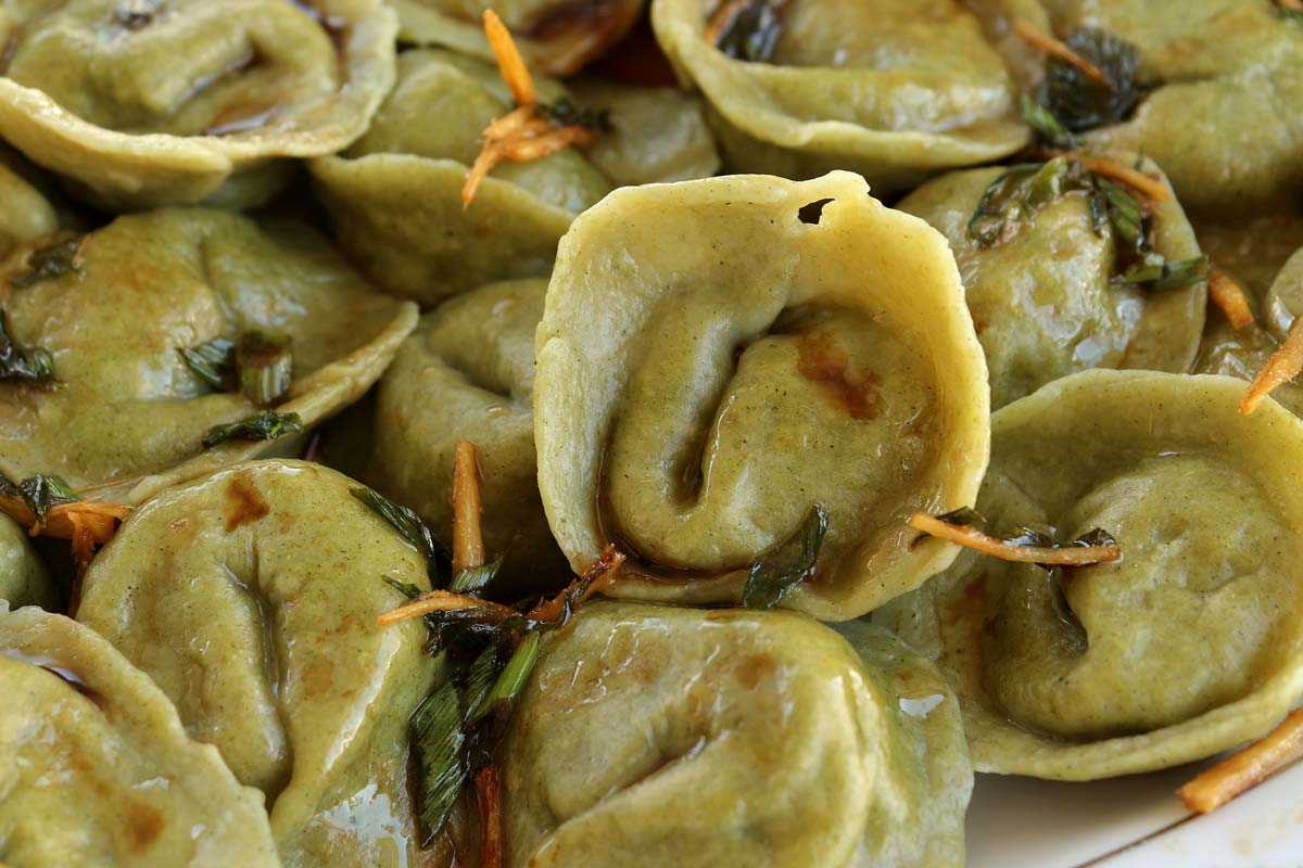 Closeup of green tortellini-shaped dumplings topped with ginger slivers, scallions, and soy sauce.