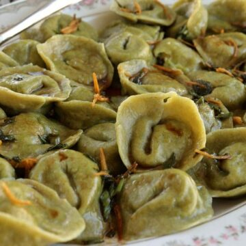 A platter of green tortellini-shaped fish dumplings topped with ginger soy sauce.