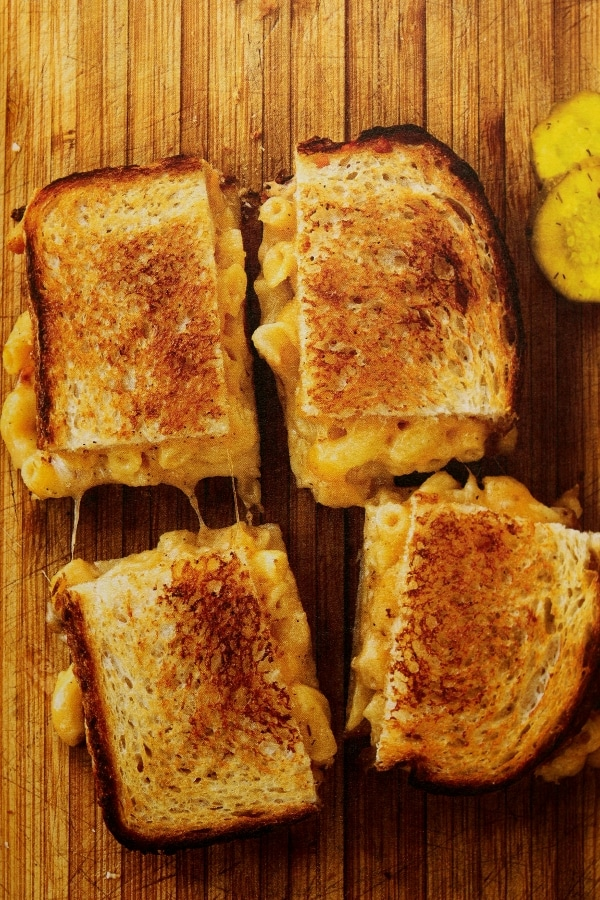a macaroni and cheese grilled cheese sandwich on a wood board