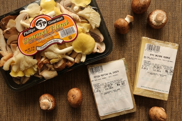 a package of mixed mushrooms and two blocks of cheese on a brown surface