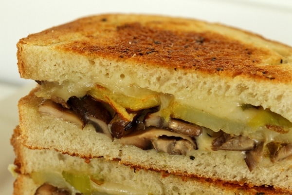 A close up of a sandwich with mushroom, potato, and cheese filling