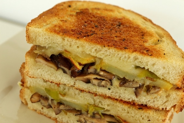 a closeup of a halved mushroom grilled cheese sandwich