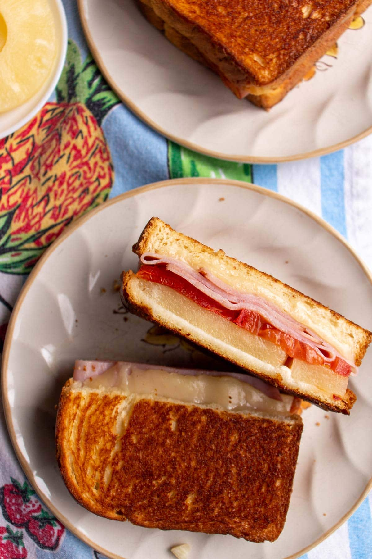 A halved grilled cheese sandwich on a plate showing off the ham and pineapple filling.
