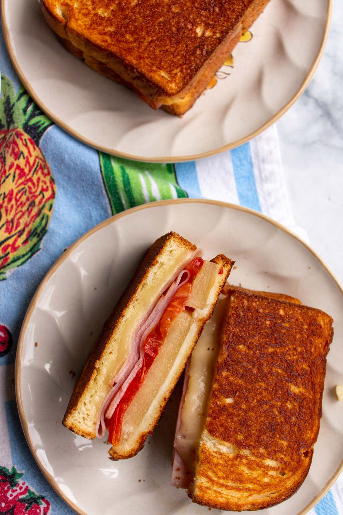 A halved Hawaiian grilled cheese sandwich on a plate showing off the ham and pineapple filling.