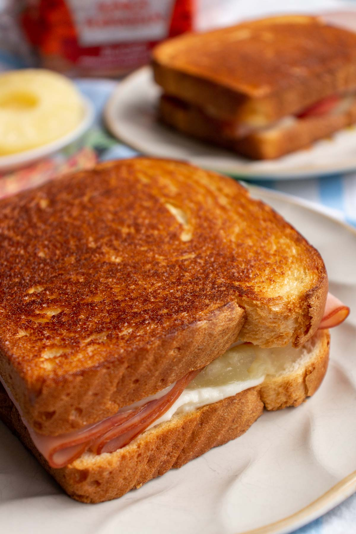 Closeup of a grilled cheese sandwich with ham and pineapple in the filling.