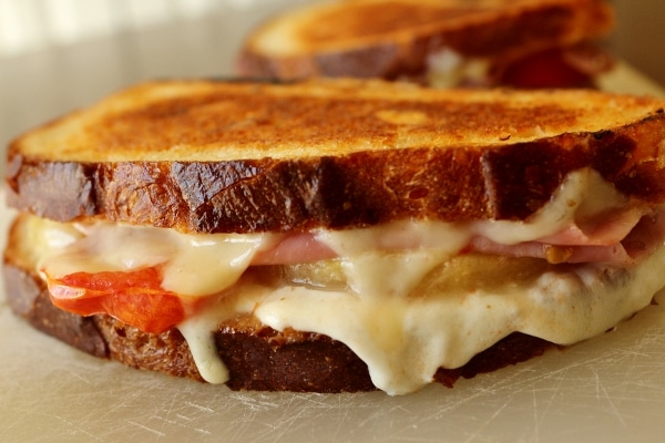 A close up of a grilled cheese sandwich with ham, pineapple, and tomato inside