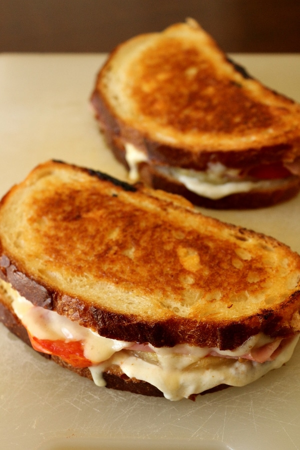 two golden brown grilled cheese sandwiches on a white cutting board