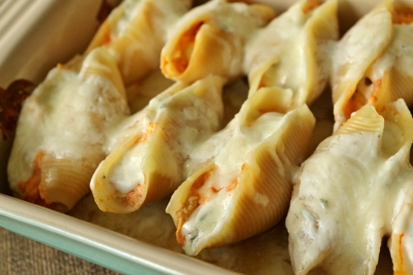A close up side view of baked buffalo chicken stuffed shells