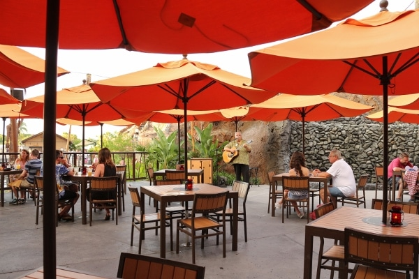 a bunch of outdoor dining tables with orange umbrellas