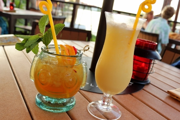 two tropical drinks with curly straws on an outdoor table