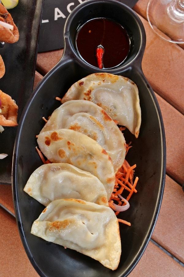 pan-fried dumplings served on a black plate