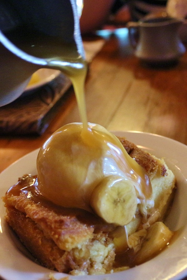 a plate of bread pudding with ice cream and banana sauce being poured over the top