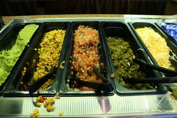 a buffet style area with toppings for Mexican food
