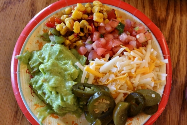 A plate of toppings like guacamole, jalapenos, tomato, and shredded cheese